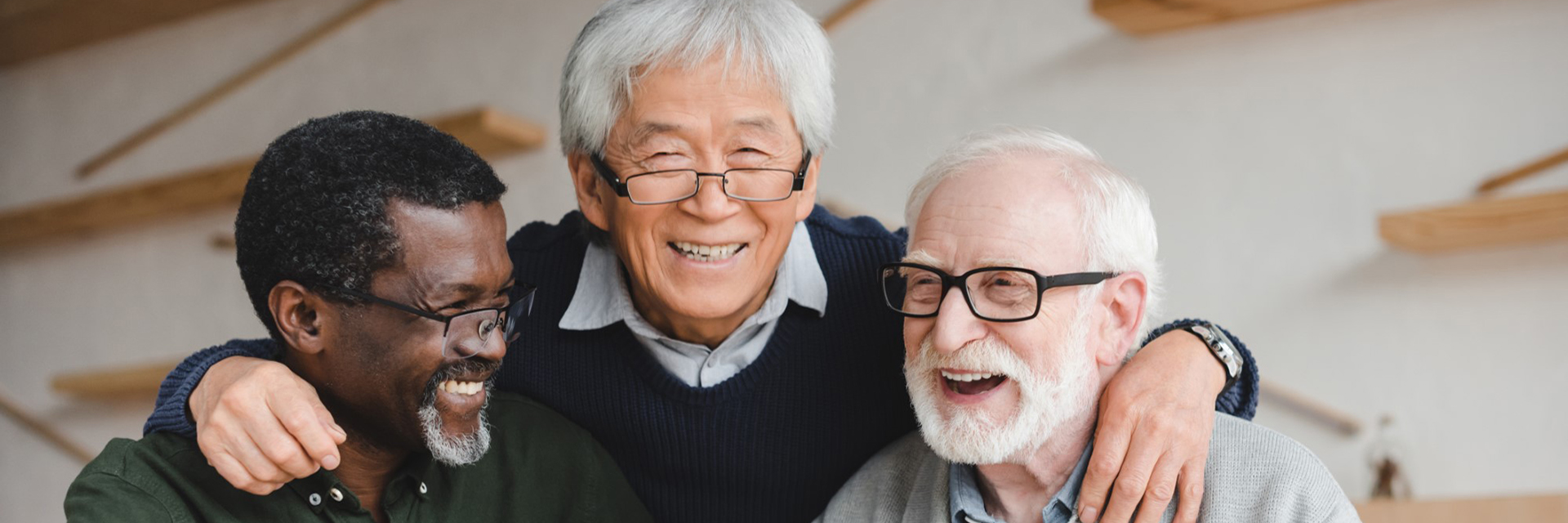 three men in glasses smiling arms around each other